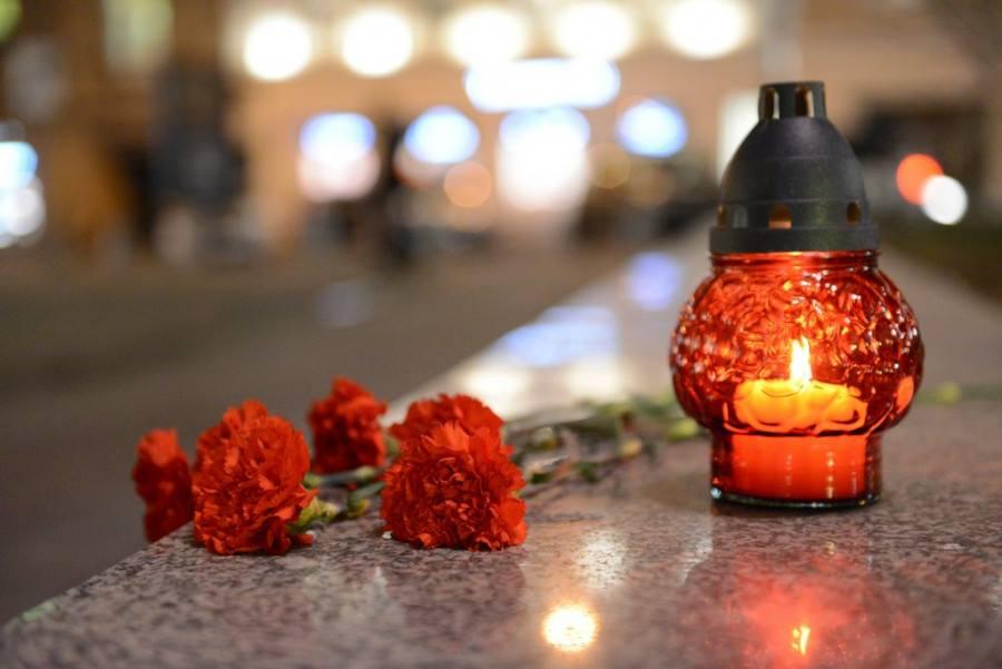 Горящая лампада и цветы на гранитной плите