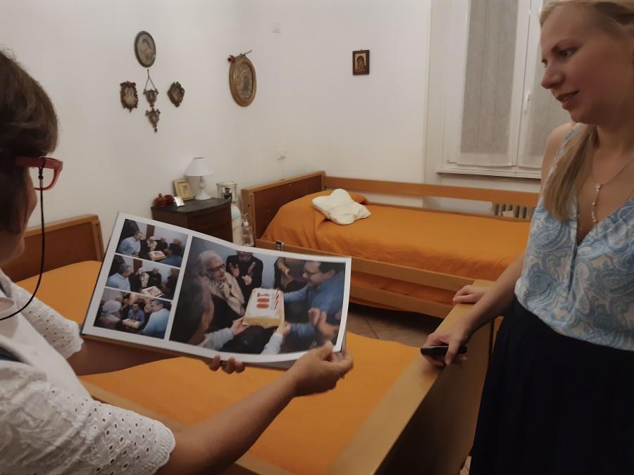 Николетта Д'Алессандро, член общины и многолетний помощник в доме совместного проживания, показывает фотографии и рассказывает нам, как самые больные пожилые люди начинали снова ходить, когда благодаря общению к ним возвращались смысл и радость жизни. Дом становится домом для всех, здесь празднуют дни рождения не только пожилых людей, но и помощников. Жители дома становятся настоящими бабушками и дедушками для детей волонтёров