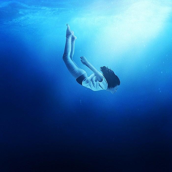 Девушка под водой красиво плывет