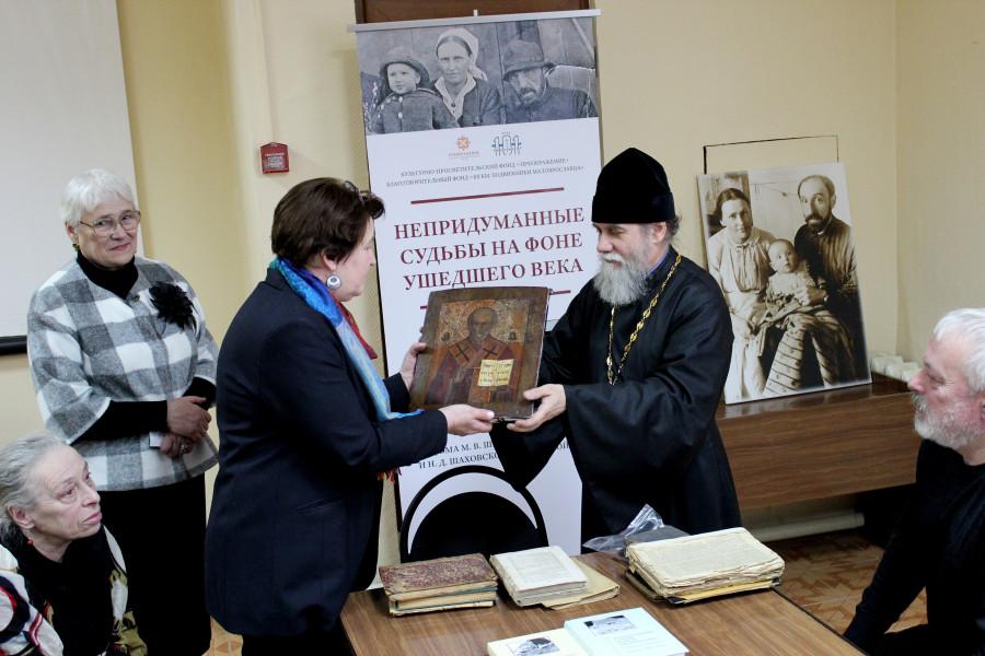 Протоиерей Андрей Лобашинский передает Елене Старостенковой икону и книги в дар фонду «101 км. Подвижники Малоярославца»