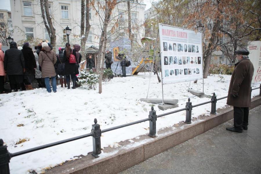 Человек стоит у стенда с фотографиями погибших