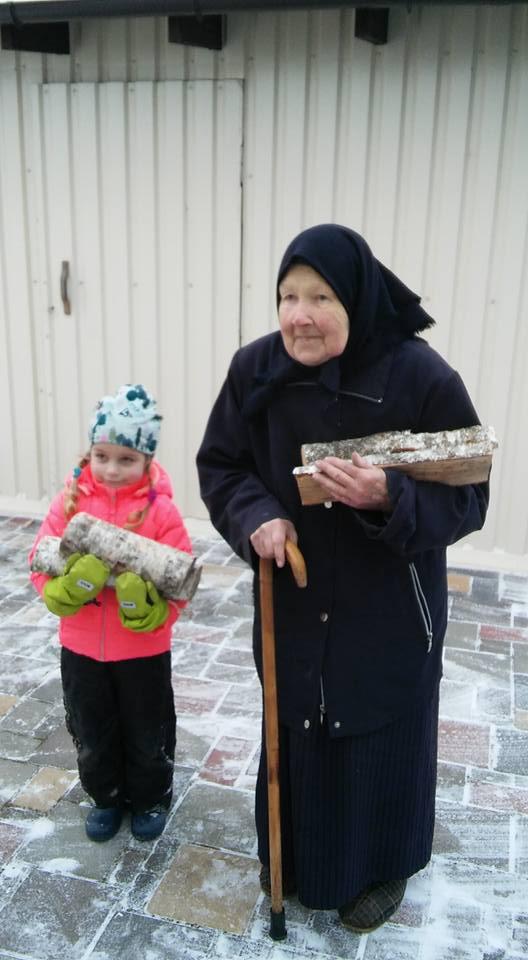 Матушка и маленькая девочка на улице, обе держат поленья