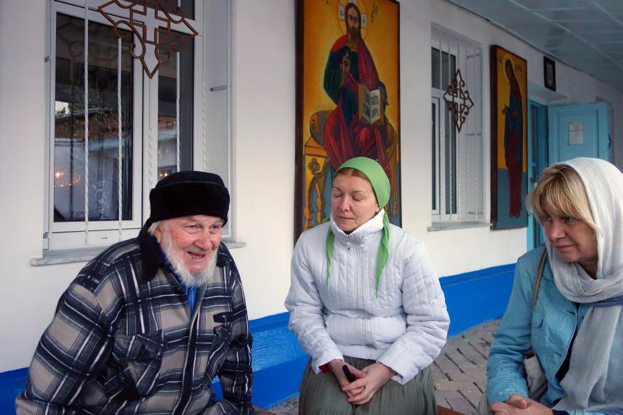 Беседа с отцом Димитрием Козулиным у Георгиевского храма. На заднем плане – иконы, написанные Алексеем Петровичем Арцыбушевым