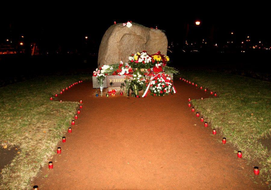 По краям дорожки к Соловецкому камню стоит множество свечей, у камня - букеты цветов