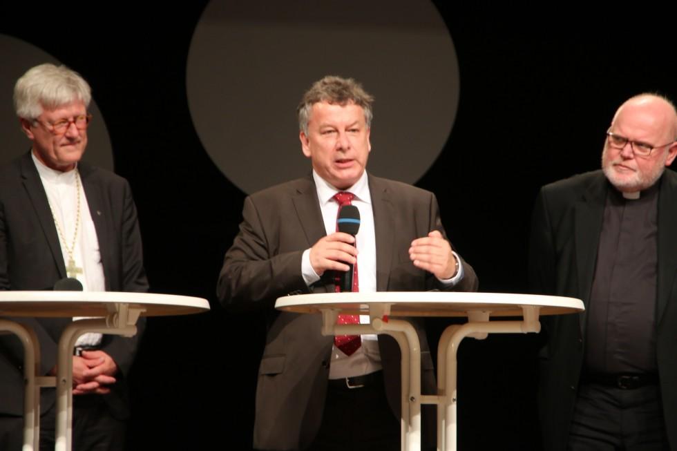 Пастор Томас Рёмер (ИМКА Мюнхен, Евангелическо-лютеранская церковь Баварии); епископ Генрих Бедфорд-Штром, председатель совета Евангелической церкви Германии (слева); Кардинал Рейнхард Маркс, председатель Конференции католических епископов Германии (справа)
